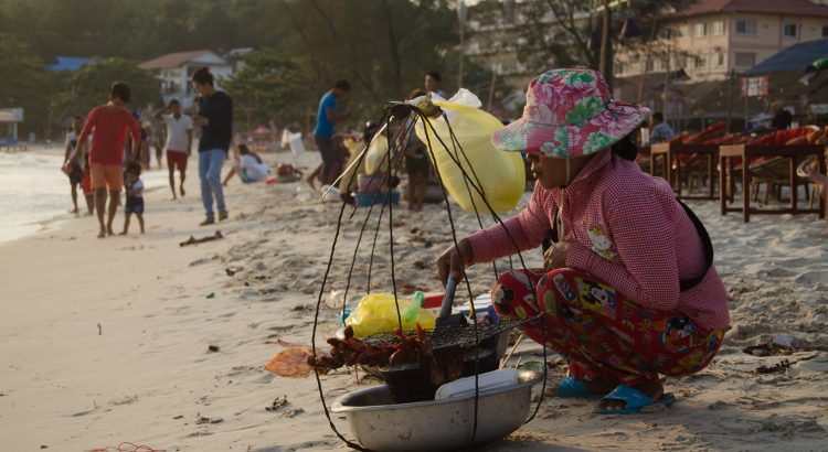 Woman selling grilled squid in Sihanoukville beach, Cambodia