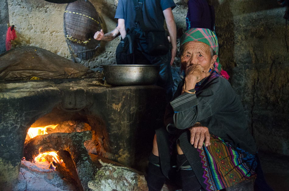 Old vietnamese woman near a wood stove